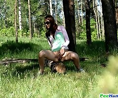 Cute babe pisses onto a fallen tree in the forest